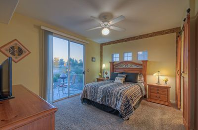 Attractive master bedroom has queen bed, view of golf course and sliding doors to patio