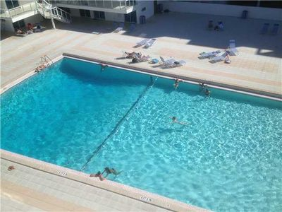 Large swimming pool with tiki bar located just steps from the ocean side.