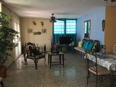 Living room with TV set and dinner room. There are two Ceiling fans
