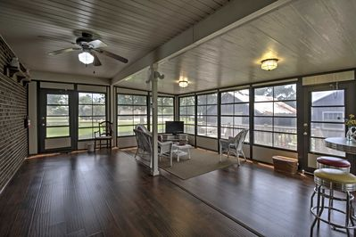 The sunroom is the perfect place to relax and watch TV as you admire the surrounding views out the wall of windows.