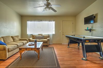 The home features wooden floors, comfortable furnishings & an air hockey table.