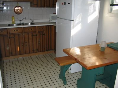 Dining kitchen area with fridge stove and microwave Bench seating for 4