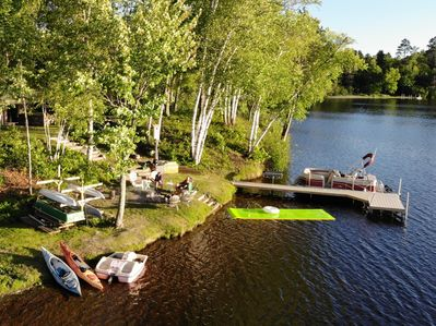 Waterfront fire pit and chairs, grill, dock, lily pad and boat rack and 7 boats