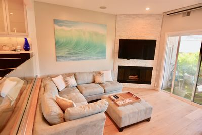 Bright living room with large flat screen TV with cable and streaming