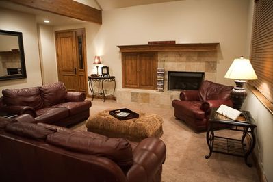 Living room on main level with gas fireplace, TV (in cabinet) and half bath door