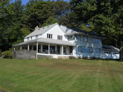 Main house with sweeping front lawn and covered porch.