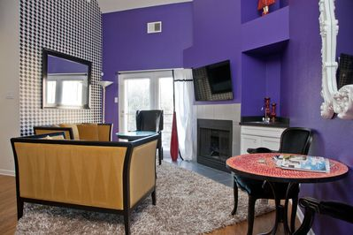 The living room has a fireplace, balcony, wet bar, and flat screen television.