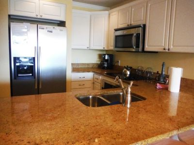 Kitchen has granite counter tops, stainless appliances bar seating.