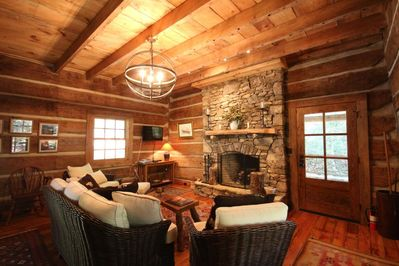 Living area, fireplace, couch, heavy beams, authentic cabin.