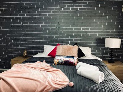 King Bed with grey brick feature wall