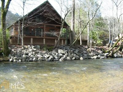 Photo for This Log Cabin Home sits literally on the banks of the Chattahoochee River in downtown Helen. It's a