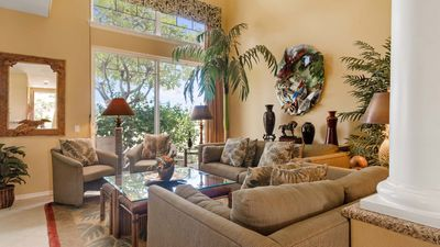 Living room with Hawaiian inspired decor, large window, and olive green couches