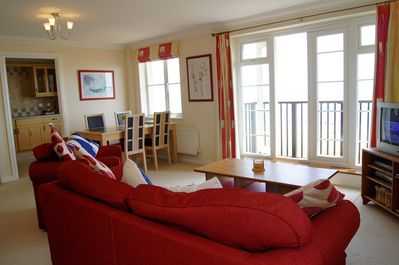 Spacious open-plan living with sea views, double french doors to balcony