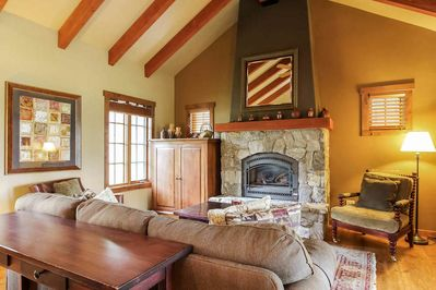 Living room seating surrounding a stone fireplace