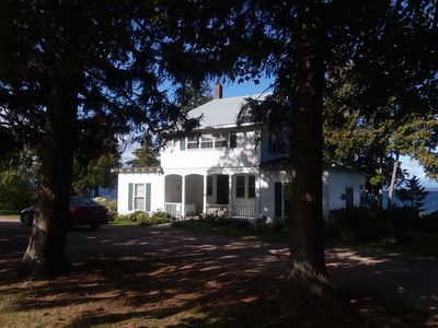 The front of the house as you drive down the tree lined driveway.