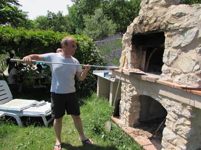 Making pizza in the wood-fired oven by the pool