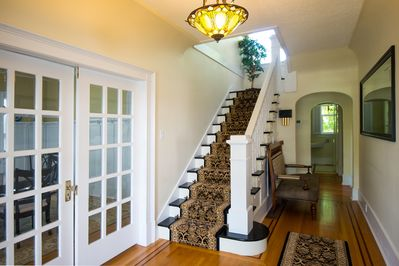 Elegant foyer and handcrafted staircase. Original oak hardwood floors.
