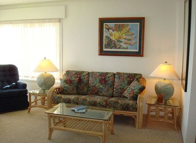 The living room with its comfortable rattan sofa and swivel chairs.