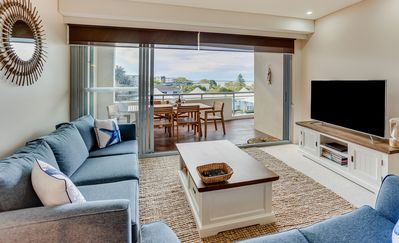 Lounge with flat screen TV and water views.