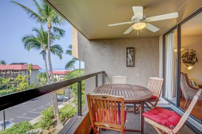 Spacious lanai with outdoor dining and side ocean view, with ceiling fan.