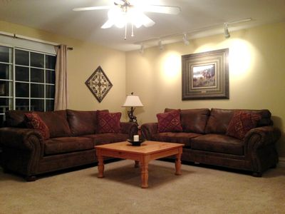 Two couches, one is queen sleeper sofa, balcony, ceiling fan