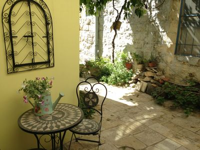 Quiet, secluded courtyard outside Hobbit Cottage is shaded by an orange tree.