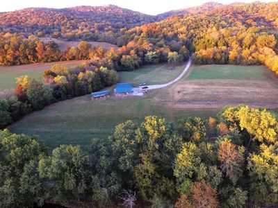 Drone over river looking back at the farm.