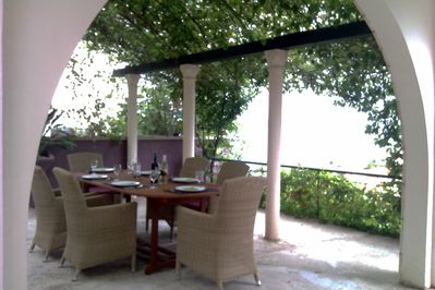 Courtyard dining area with sea view and shade