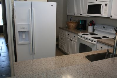 Updated kitchen with solid surface countertops and new appliances.
