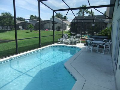 Patio dining and loungers for sunbathing. Hot tub on pool deck.