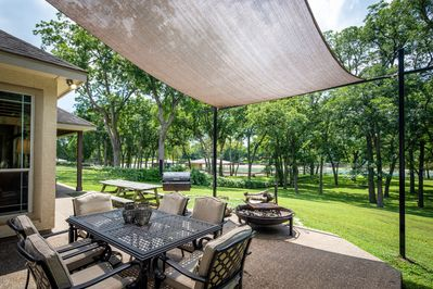 PECAN SHORES RETREAT - a SkyRun Texas Property - Back patio with seating, campfire pit, and river view