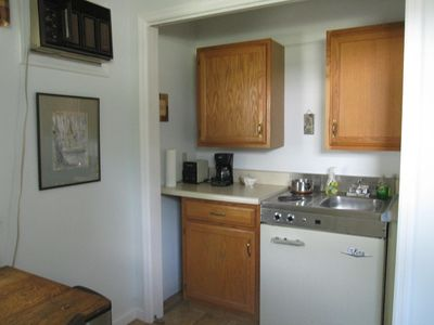 Kitchenette on one wall of the living room. Stove, Sink, Small Fridge!