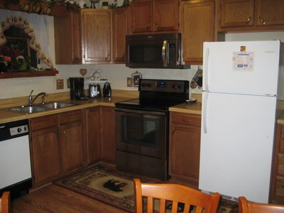 Full size kitchen with all utensils and dining table.