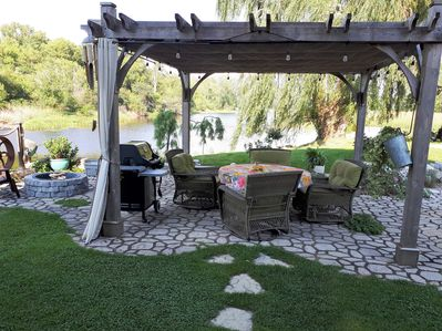 Patio by the river with Weber bbq, cushioned, swivel chairs, firepit & hot tub.