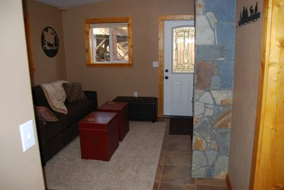 Cozy cabin entry with queen sleeper sofa and laundry room
