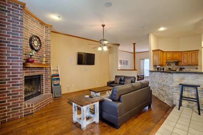 Living room with couch, love seat, 55 inch TV and gas fireplace