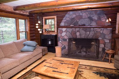 The living room is gorgeous with a fieldstone fireplace and view of the river.