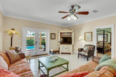 """Living Room - Watch your favorite shows on the 42"""" TV or simply enjoy views of the gorgeous pool in the main house living room."""