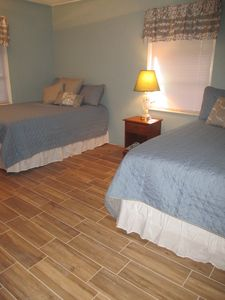 master, 2 double beds, showing tile wood plank flooring all throughout cottage.
