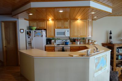 From the fully equipped kitchen, look across the living room to the lake