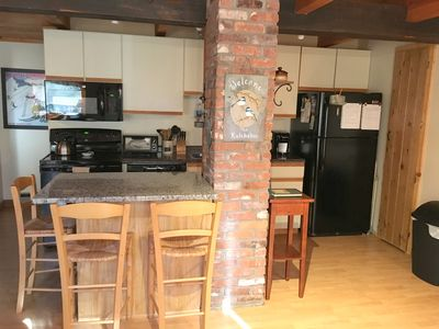 fully applianced and stocked kitchen with granite island seating for 3