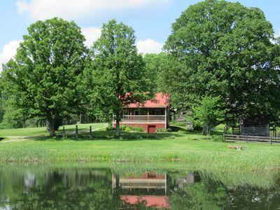 This cabin has oak trees surrounding it, plus a pleasant view of a backyard pond