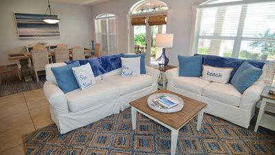 Open concept living and dining areas with coastal furnishings