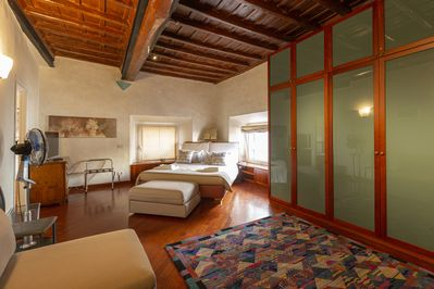 The king size comfortable bed under the coffered ceiling of the master bedroom
