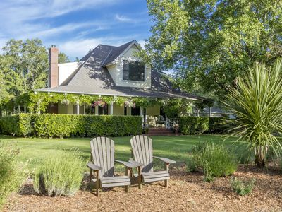 Distinctive farmhouse with wraparound veranda set on nearly four private acres