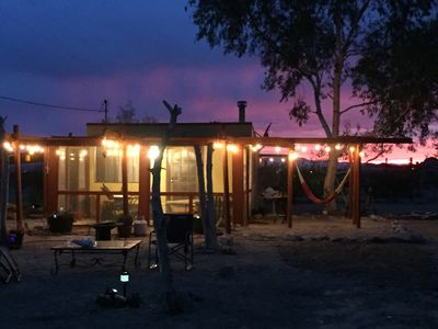 El Ranchito at night with a prototypical Joshua Tree sunset in the background.