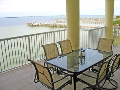 Sweeping Bay views from large balcony with full eating area and lounge chairs.