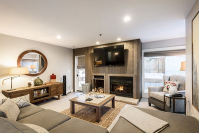 """Living Room with 65"""" Smart TV, Wood Burning Fireplace, Patio Access, and Mountain Contemporary Furnishings"""
