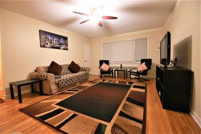 Large living room with 50 inch flat screen TV, sofa and chairs