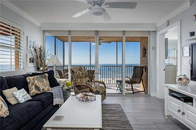 The living room's view is spectacular - The airy living room opens onto the balcony, which in turn overlooks the soft white sands and the serene Fort Myers Beach.
